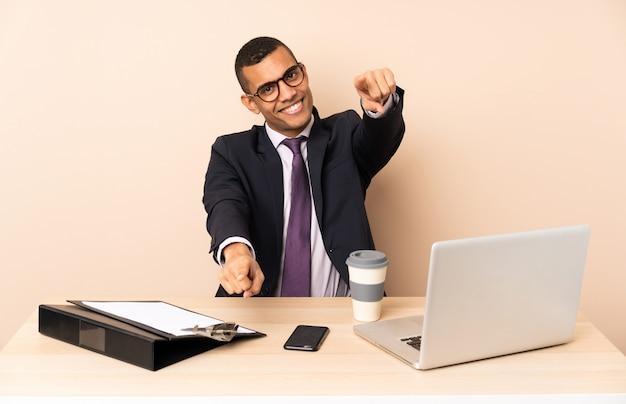 Homem de negócios jovem em seu escritório com um laptop e outros documentos aponta o dedo para você enquanto sorrindo