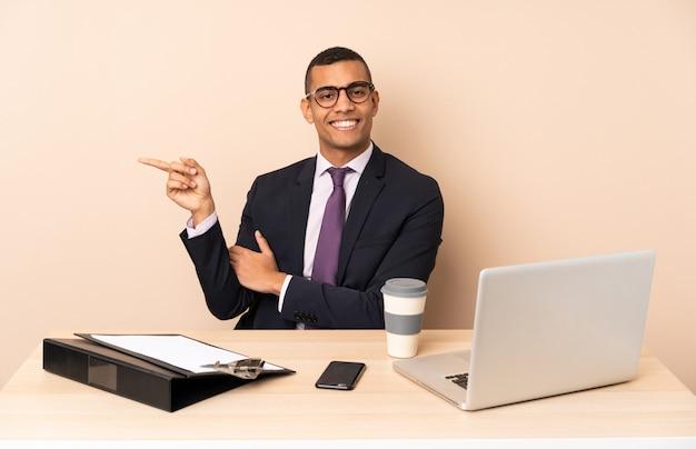 Homem de negócios jovem em seu escritório com um laptop e outros documentos apontando o dedo para o lado