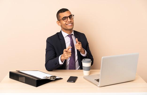 Homem de negócios jovem em seu escritório com um laptop e outros documentos apontando para a frente e sorrindo