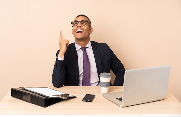 Homem de negócios jovem em seu escritório com um laptop e outros documentos apontando para cima e surpreso