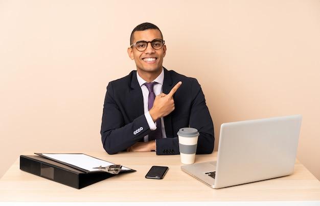 Homem de negócios jovem em seu escritório com um laptop e outros documentos apontando para o lado para apresentar um produto