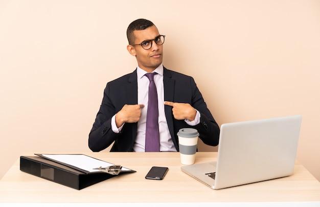 Homem de negócios jovem em seu escritório com um laptop e outros documentos apontando para si mesmo