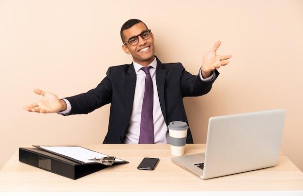 Homem de negócios jovem em seu escritório com um laptop e outros documentos apresentando e convidando para vir com a mão
