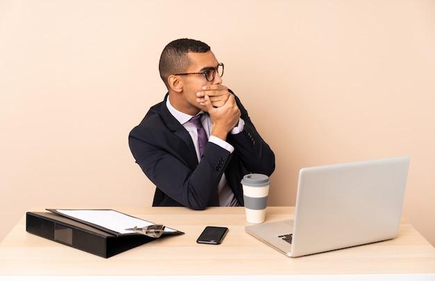 Homem de negócios jovem em seu escritório com um laptop e outros documentos cobrindo a boca e olhando para o lado