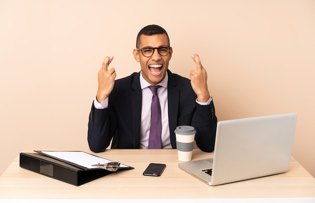 Homem de negócios jovem em seu escritório com um laptop e outros documentos com cruzando os dedos
