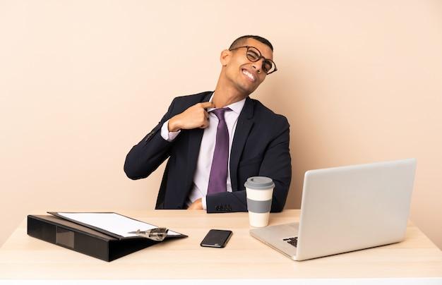 Homem de negócios jovem em seu escritório com um laptop e outros documentos com expressão de cansado e doente