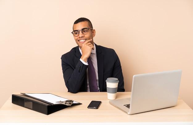 Homem de negócios jovem em seu escritório com um laptop e outros documentos olhando para o lado