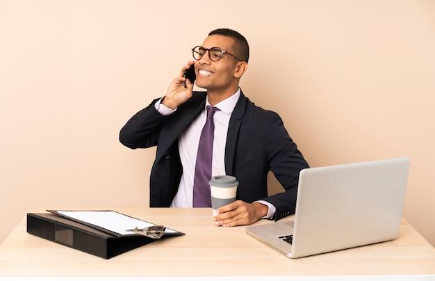 Homem de negócios jovem em seu escritório com um laptop e outros documentos segurando café para levar e um celular