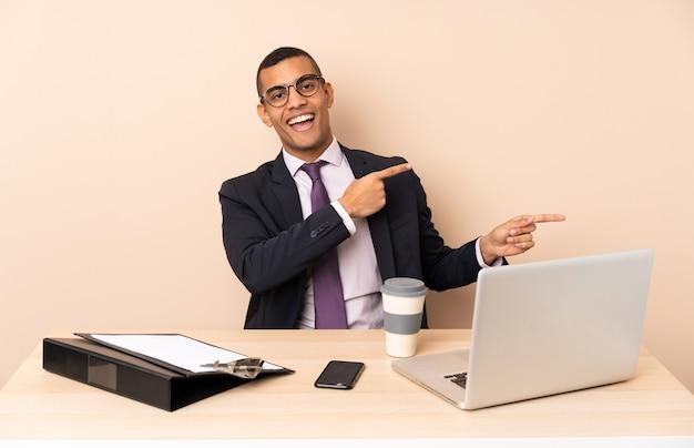 Homem de negócios jovem em seu escritório com um laptop e outros documentos surpreso e apontando o lado
