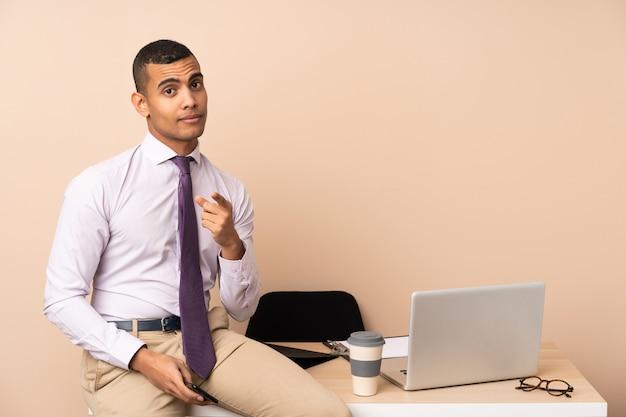 Homem de negócios jovem em um escritório aponta o dedo para você