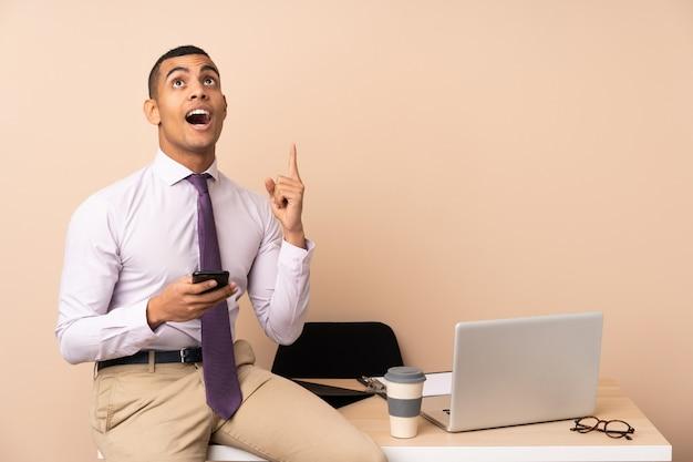 Homem de negócios jovem em um escritório, apontando com o dedo indicador uma ótima idéia