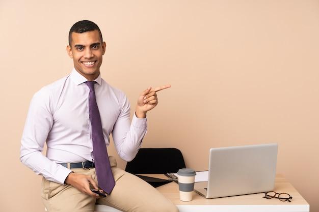 Homem de negócios jovem em um escritório, apontando o dedo para o lado