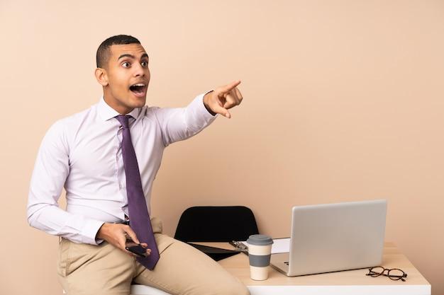 Homem de negócios jovem em um escritório apontando para fora