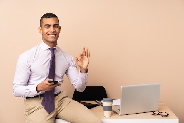 Homem de negócios jovem em um escritório, mostrando um sinal de ok com os dedos