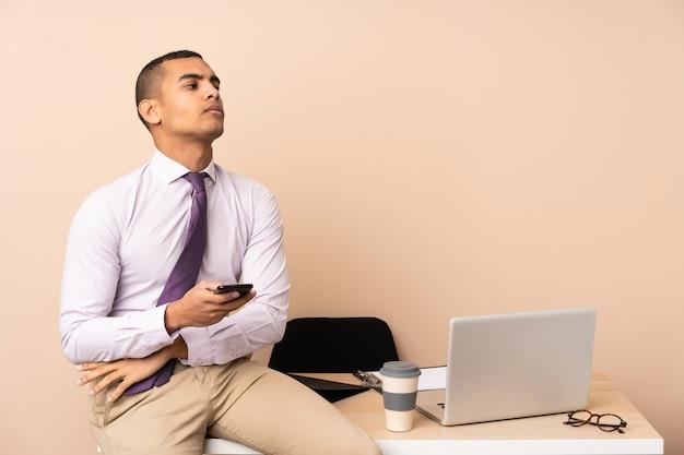 Homem de negócios jovem em um escritório, pensando em uma idéia