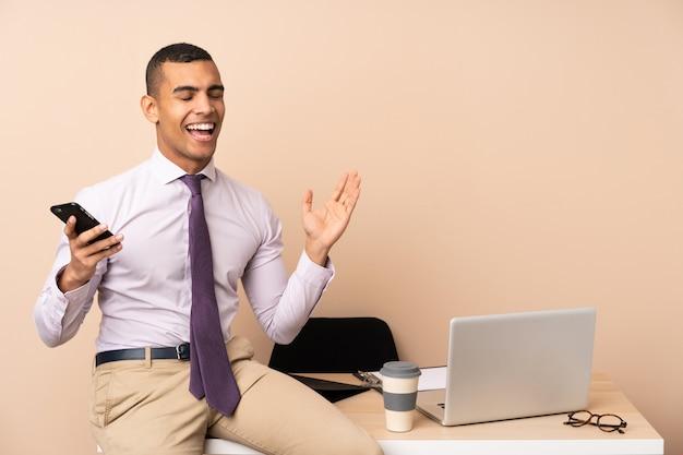 Homem de negócios jovem em um escritório rindo