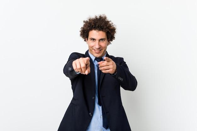Homem de negócios jovem encaracolado contra sorrisos alegres de parede branca, apontando para a frente.
