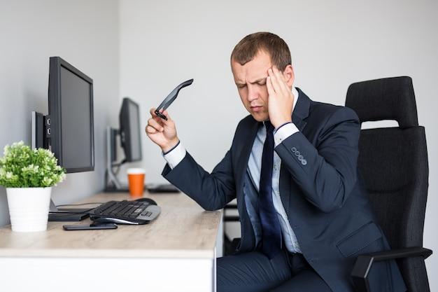 Homem de negócios jovem estressado com dor de cabeça trabalhando em um escritório moderno