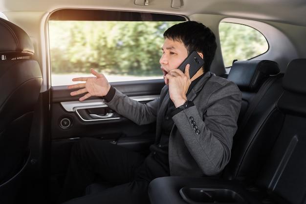 Homem de negócios jovem estressado falando sobre o problema em um telefone celular enquanto está sentado no banco de trás do carro