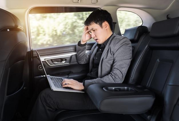 Homem de negócios jovem estressado usando um laptop enquanto está sentado no banco de trás do carro