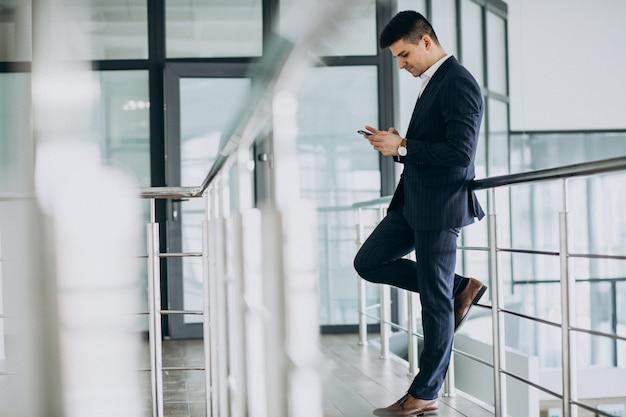 Homem de negócios jovem falando no telefone no escritório
