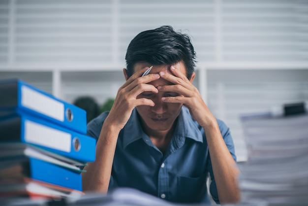 Homem de negócios jovem fazendo relatórios financeiros, sentindo o estresse com a pilha de papéis.