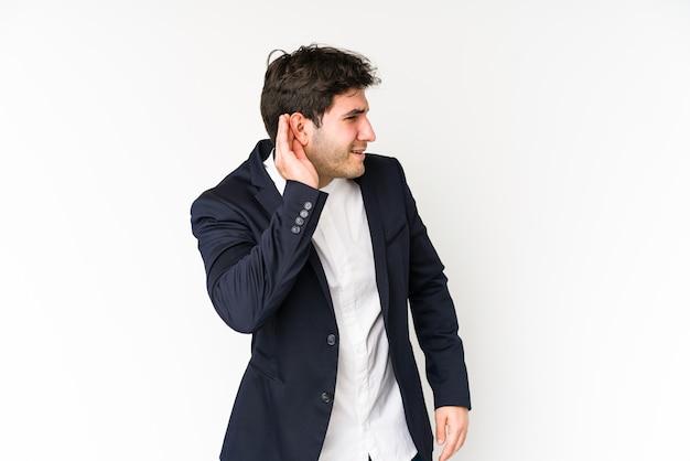 Homem de negócios jovem isolado no branco, tentando ouvir uma fofoca.