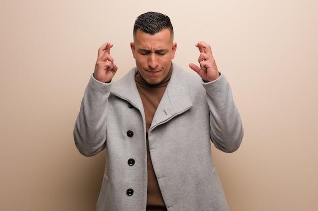 Homem de negócios jovem latina, cruzando os dedos por ter sorte