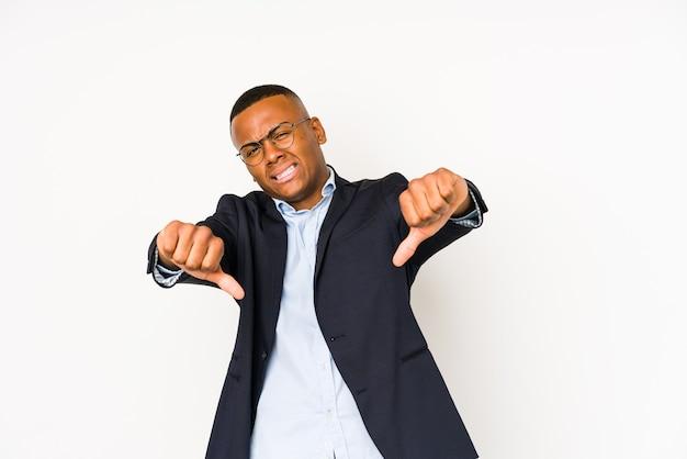 Homem de negócios jovem latino isolado no branco, mostrando o polegar para baixo e expressando antipatia.