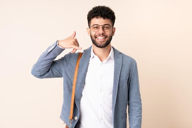 Homem de negócios jovem marroquino isolado em fundo bege, fazendo gesto de telefone. ligue-me de volta sinal