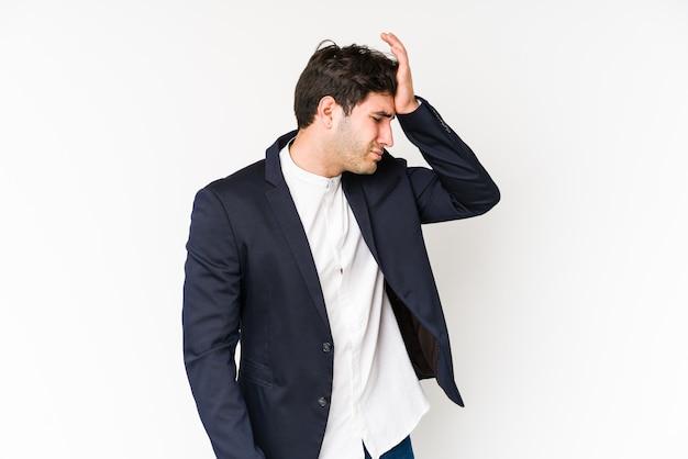 Homem de negócios jovem na parede branca, tapa na testa com palma e fechar os olhos.