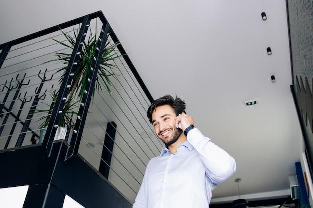 Homem de negócios jovem nas escadas no escritório