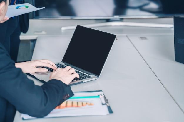 Homem de negócios jovem positivo sentado e trabalhando com documentos e laptop,
