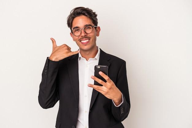 Homem de negócios jovem raça mista segurando o telefone móvel isolado no fundo branco, mostrando um gesto de chamada de telefone móvel com os dedos.