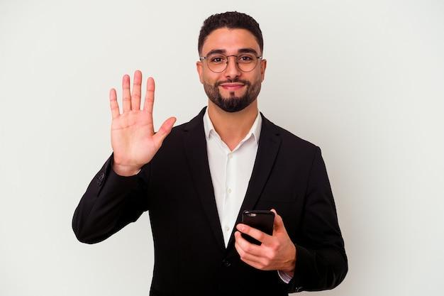 Homem de negócios jovem raça mista segurando um homem de telefone móvel isolado no fundo branco, sorrindo alegre mostrando o número cinco com os dedos.
