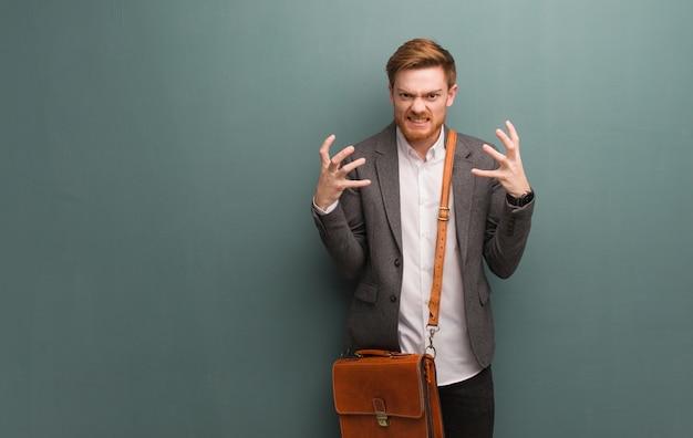 Homem de negócios jovem ruiva com raiva e chateado