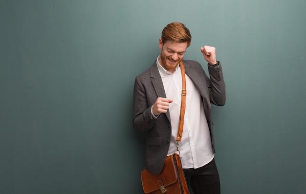Homem de negócios jovem ruiva dançando e se divertindo