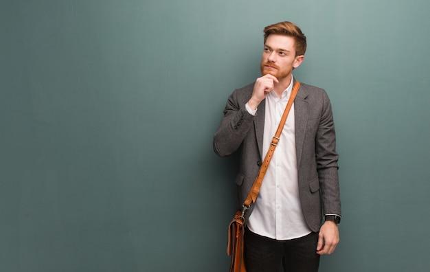 Homem de negócios jovem ruiva duvidando e confuso