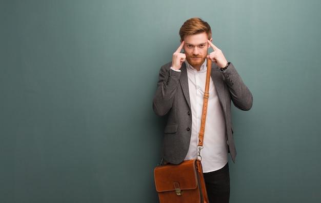 Homem de negócios jovem ruiva fazendo um gesto de concentração