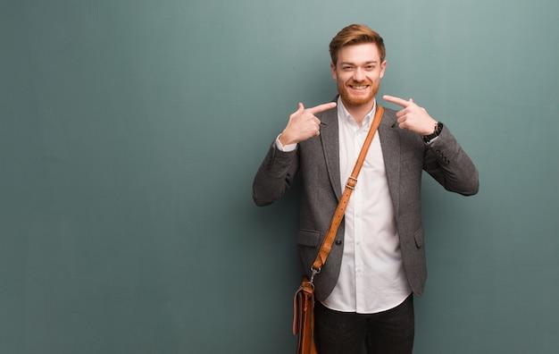 Homem de negócios jovem ruiva sorri, apontando a boca