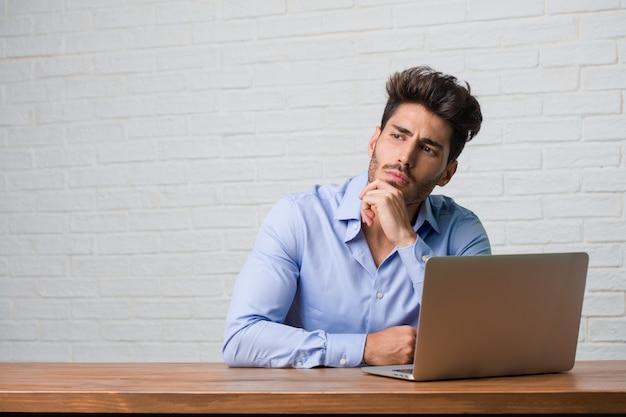 Homem de negócios jovem sentado e trabalhando em um laptop, duvidando e confuso