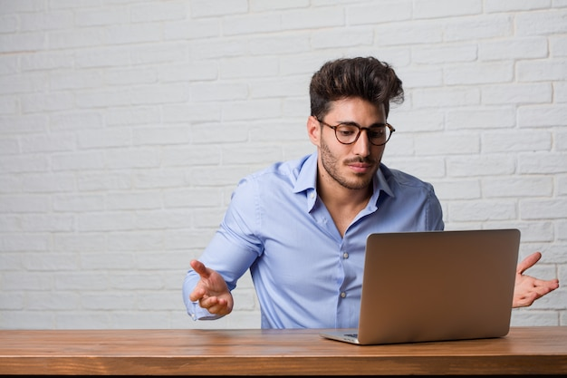 Homem de negócios jovem sentado e trabalhando em um laptop duvidando e encolher os ombros