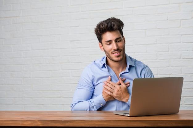 Homem de negócios jovem sentado e trabalhando em um laptop, fazendo um gesto romântico