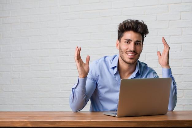 Homem de negócios jovem sentado e trabalhando em um laptop, rindo e se divertindo, sendo relaxado e alegre, sente-se confiante e bem sucedido