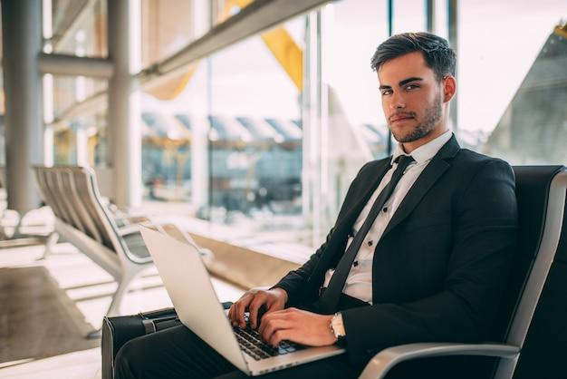 Homem de negócios jovem sentado no computador com a mala no aeroporto esperando o voo