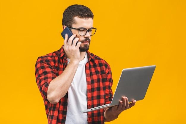 Homem de negócios jovem sério em casual com um laptop sentado no chão chamando com telefone inteligente.