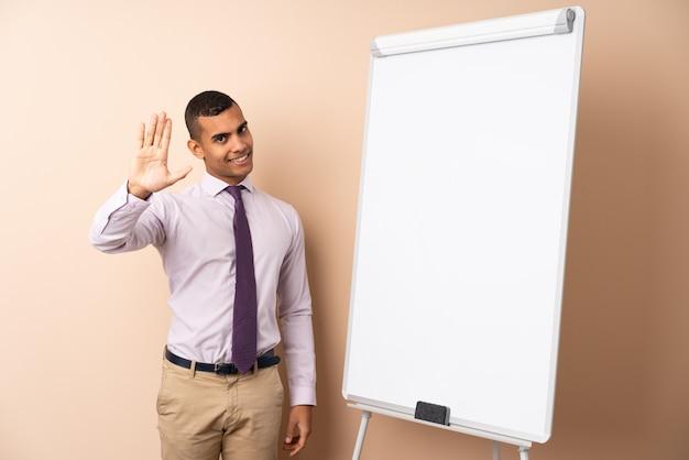 Homem de negócios jovem sobre parede isolada, dando uma apresentação no quadro branco e saudando com a mão