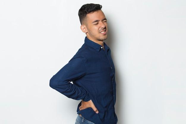 Homem de negócios jovem sofrendo de dor lombar e dor lombar na cintura em fundo branco