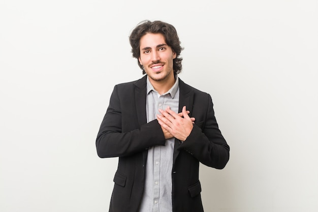 Homem de negócios jovem tem expressão amigável, pressionando a palma da mão no peito