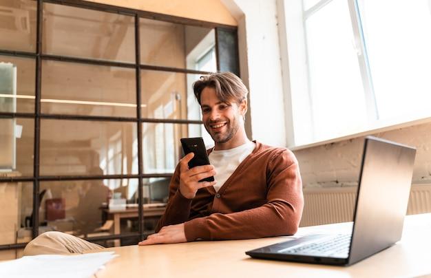 Homem de negócios jovem trabalhando no escritório. empregador inicial sentado em sua estação de trabalho